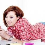 happy red hair student, business woman lying down working on laptop